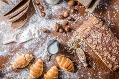 En la panadería, aún la vida con los mini cruasanes, el pan, la leche, las nueces y la harina Foto de archivo