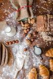 En la panadería, aún la vida con los mini cruasanes, el pan, la leche, las nueces y la harina Imagenes de archivo