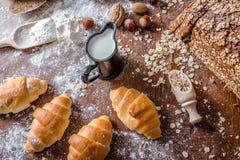 En la panadería, aún la vida con los mini cruasanes, el pan, la leche, las nueces y la harina Fotografía de archivo