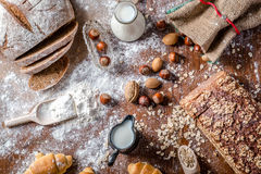 En la panadería, aún la vida con los mini cruasanes, el pan, la leche, las nueces y la harina Fotografía de archivo libre de regalías