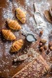 En la panadería, aún la vida con los mini cruasanes, el pan, la leche, las nueces y la harina Fotos de archivo