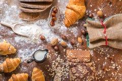En la panadería, aún la vida con los mini cruasanes, el pan, la leche, las nueces y la harina Imagen de archivo libre de regalías