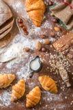 En la panadería, aún la vida con los mini cruasanes, el pan, la leche, las nueces y la harina Foto de archivo libre de regalías
