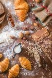 En la panadería, aún la vida con los mini cruasanes, el pan, la leche, las nueces y la harina Imágenes de archivo libres de regalías
