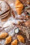 En la panadería, aún la vida con los mini cruasanes, el pan, la leche, las nueces y la harina Fotos de archivo libres de regalías