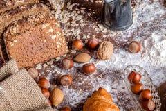 En la panadería, aún la vida con pan, las nueces y la harina Fotografía de archivo libre de regalías