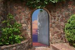 En la pared de piedra hermosa la puerta del hierro es entornada Fotos de archivo