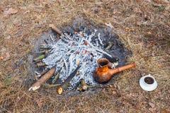 En la participación en el bosque de la primavera, un pote del café turco de la arcilla se calienta contra la hierba fotos de archivo libres de regalías
