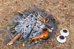 En la participación en el bosque de la primavera, un pote del café turco de la arcilla se calienta contra la hierba fotos de archivo