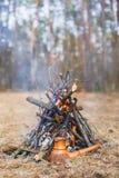 En la participación en el bosque de la primavera, un pote del café turco de la arcilla se calienta contra la hierba foto de archivo libre de regalías
