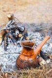 En la participación en el bosque de la primavera, un pote del café turco de la arcilla se calienta contra la hierba imagen de archivo