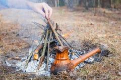 En la participación en el bosque de la primavera, un pote del café turco de la arcilla se calienta contra la hierba En la mano de fotografía de archivo