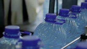 En la planta de fabricación botella de agua plástica llena que va con la tapa transparente almacen de video
