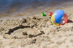 En la playa cerca del agua, construida el ` s un castillo de la arena y de una bola y de los niños de la mentira buckets Fotos de archivo libres de regalías