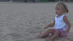 En la playa el bebé hermoso en una camiseta blanca lanza una bola anaranjada grande en la dirección almacen de metraje de vídeo