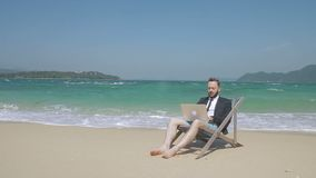 En la playa el hombre joven detrás del ordenador portátil hace un negocio el día de fiesta