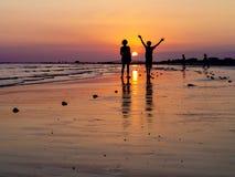 En la playa en la puesta del sol Fotos de archivo libres de regalías