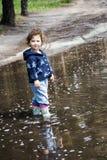 En la primavera de la niña divertida que se coloca en una piscina del caucho Foto de archivo libre de regalías