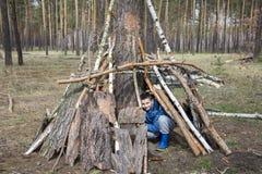 En la primavera en un bosque del pino, el muchacho construyó una choza de palillos Imagen de archivo libre de regalías
