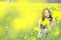 En la primavera temprana hermosa, un soporte de la mujer joven en el medio de las flores amarillas de la violación archivó que es fotos de archivo