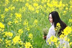 En la primavera temprana hermosa, un soporte de la mujer joven en el medio de las flores amarillas de la violación archivó que es imagenes de archivo