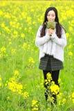 En la primavera temprana hermosa, un soporte de la mujer joven en el medio de las flores amarillas de la violación archivó que es fotografía de archivo libre de regalías