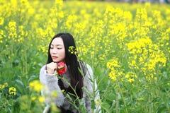 En la primavera temprana hermosa, un soporte de la mujer joven en el medio de las flores amarillas de la violación archivó que es imágenes de archivo libres de regalías
