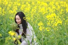En la primavera temprana hermosa, un soporte de la mujer joven en el medio de las flores amarillas de la violación archivó que es foto de archivo