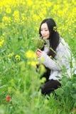 En la primavera temprana hermosa, un soporte de la mujer joven en el medio de las flores amarillas de la violación archivó que es foto de archivo libre de regalías