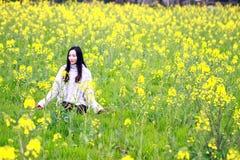 En la primavera temprana hermosa, un soporte de la mujer joven en el medio de las flores amarillas de la violación archivó que es imagen de archivo