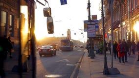 En la puesta del sol en gente que camina de la acera, en los coches ocupados y los autobuses de una impulsión del camino metrajes
