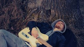En la puesta del sol, un hombre miente debajo de un roble y toca la guitarra metrajes