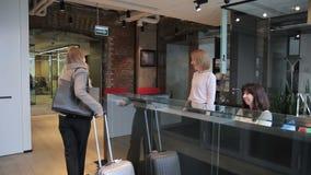 En la recepción el personal del hotel saluda la mujer con la maleta feliz almacen de video
