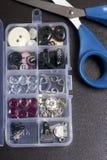 En la superficie de la tabla es una caja con los accesorios de costura Al lado de algunas bobinas del hilo y de tijeras Foto de archivo libre de regalías