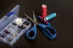 En la superficie de la tabla es una caja con los accesorios de costura Al lado de algunas bobinas del hilo y de tijeras Imágenes de archivo libres de regalías