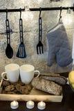 En la tabla de cocina delante de una pared gris concreta están los silbidos blancos a la guirnalda tenedor de pote colgante para  foto de archivo libre de regalías