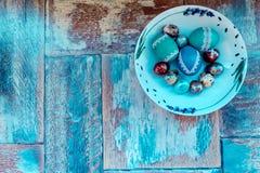 En la tabla de madera vieja es una placa de los huevos de Pascua coloreados de codornices y del pollo con los cordones coloreados Fotos de archivo