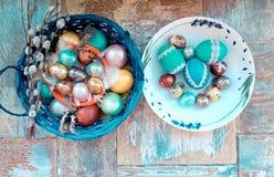 En la tabla de madera vieja es una placa de los huevos de Pascua coloreados de codornices y del pollo con los cordones coloreados Fotografía de archivo libre de regalías
