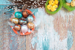 En la tabla de madera vieja es una placa de los huevos de Pascua coloreados de codornices y del pollo con los cordones coloreados Imagenes de archivo