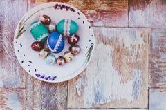 En la tabla de madera vieja es una placa de los huevos de Pascua coloreados de codornices y del pollo con los cordones coloreados Fotografía de archivo