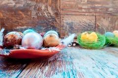 En la tabla de madera vieja es una placa de los huevos de Pascua coloreados de codornices y del pollo con los cordones coloreados Imagen de archivo libre de regalías
