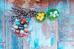 En la tabla de madera vieja es una placa de los huevos de Pascua coloreados de codornices y del pollo con los cordones coloreados Foto de archivo