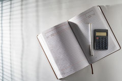 En la tabla en un diario abierto y una pluma con una calculadora Foto de archivo