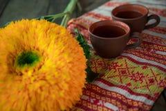En la tabla, en una toalla con las tazas del nacional de una arcilla del ornamento de té Al lado de la flor de un girasol Fotos de archivo libres de regalías