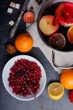 En la tabla es los arándanos, una cacerola con un vino reflexionado sobre, una naranja y un limón Visión desde arriba fotografía de archivo