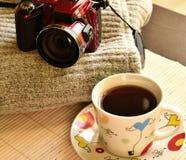 En la tabla es una taza de café del té, es después un paño de lana y una cámara imágenes de archivo libres de regalías