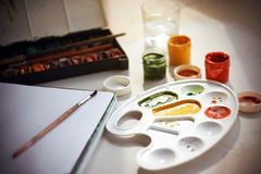 En la tabla hay pinturas de la acuarela, un cuaderno, un vaso de agua, pinturas del aguazo y cepillos foto de archivo