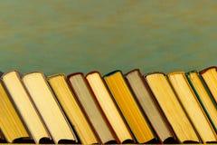 En la tabla a la serie de libros inclinados a la izquierda imágenes de archivo libres de regalías