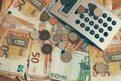 En la tabla son las monedas, los billetes, y una calculadora, imagen de archivo libre de regalías