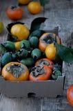En la tabla en una caja mandarines de un caqui fresco, del feijoa y de la fruta cítrica Foto de archivo